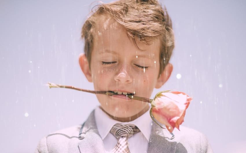 子供がバラを咥えている