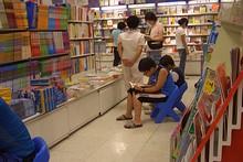 Eマートチンジュ店の書籍コーナーで立ち読みではなく、座り読みをする人々