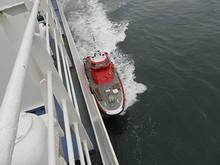水先人をこちらの船に移している所