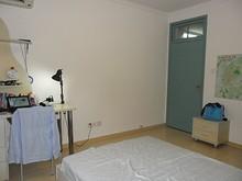 ベッドの下側に机、入口の隣にあるのは小さい引き出し