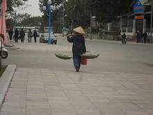 天秤棒で担いで歩く女の人。ベトナム人女性は菅笠を被ると、なんだかきれいに見える