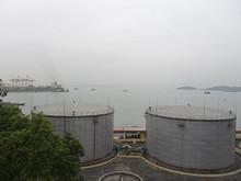 道の途中から見た石油タンクと港