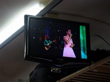 車内テレビではCAM LYのライブが流れている